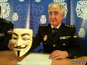 Spanish police officer holds Anonymous mask