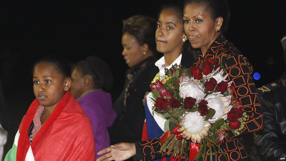 Michelle Obama and her daughters Sasha(L) and Malia (2L) arrive in South Africa (20 June 2011)