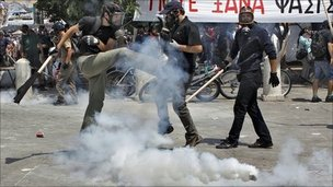 A demonstrator kicks a tear gas canister during protests against austerity measures in Athens, 28 June, 2011
