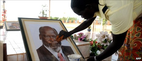 A woman cleans a portrait of the late SPLM leader John Garang at his memorial in Juba