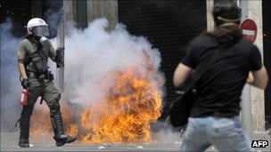 A protester faces a riot policeman in front of the Greek Parliament on 29 June 2011 in Athens as lawmakers moved towards a vote on a massive austerity package demanded by international creditors.