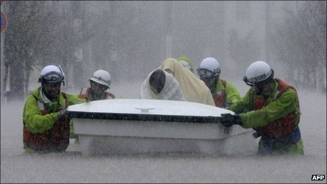 Rescue workers transport evacuees in a boat through floodwaters in Nagoya, Aichi prefecture, in central Japan