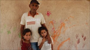 Eid Jahalin with his two daughters outside the tyre school
