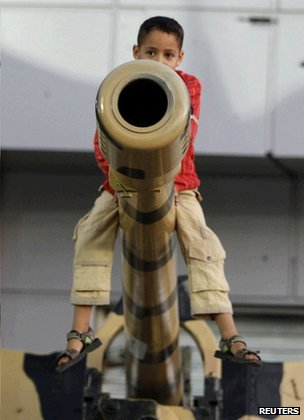 Boy perched on gun barrel