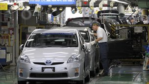 Factory worker checking an assembled Prius hybrid vehicle