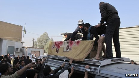 People arrange the coffin of a victim of the attack on a funeral in Baghdad, 27 January