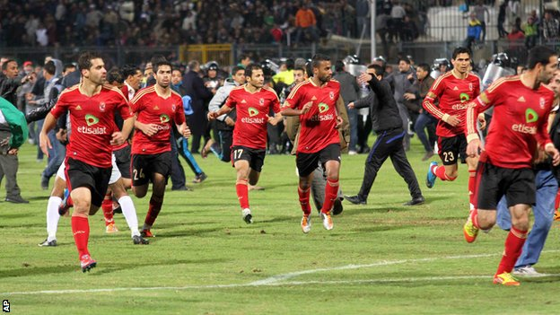 Al-Ahly players flee the pitch at the end of the game against al-Masry