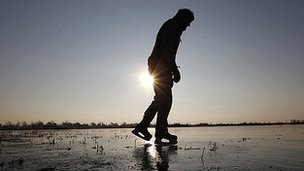A man ice skates on the frozen fens in Welney, Norfolk