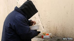 A man eats food distributed by Athens' city authorities