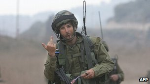 An Israeli soldier gives a photographer the finger