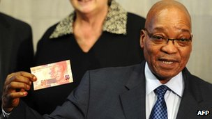 Jacob Zuma shows a new banknote bearing the image of Nelson Mandela