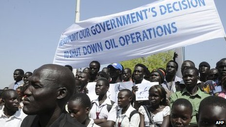 South Sudanese citizens hold banners expressing solidarity as President Salva Kiir declared a halt on all oil operations in South Sudan