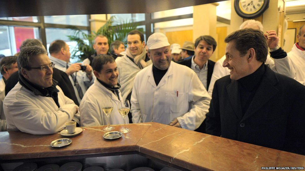 Nicolas Sarkozy (right) speaks with butchers at a cafe as he visits the Rungis wholesale market near Paris