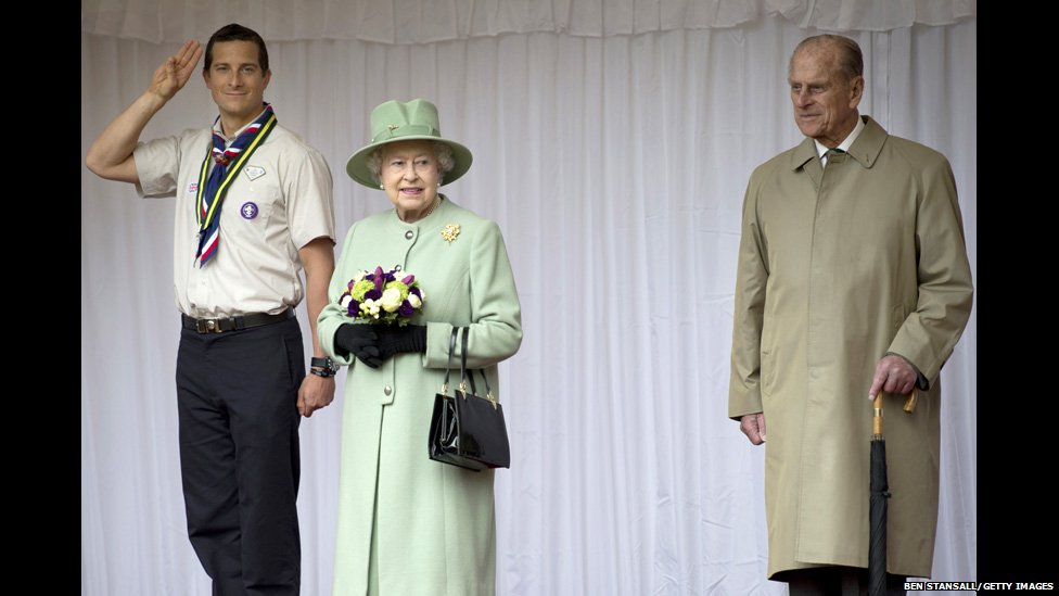 Chief Scout Bear Grylls stands with Queen Elizabeth II and Prince Philip, Duke of Edinburgh