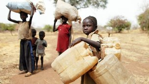 Children carry their family's belongings as they go to Yida refugee camp in South Sudan outside Tess village in the Nuba Mountains in South Kordofan, 2 May 2012