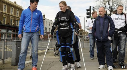 Woman with crutches and body suit walks with 3 other people