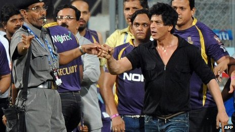 Bollywood actor Shah Rukh Khan (R) gestures towards a security guard blowing a whistle to direct children accompanying him off the playing field - 16 May
