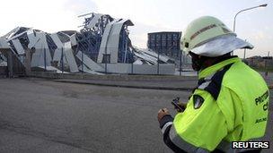 A rescue worker stands in front of a damage ceramics factory building Sant'Agostino di Ferrara