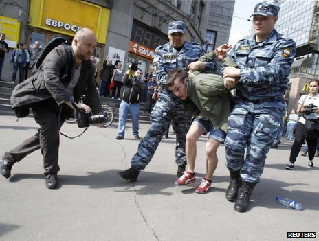 Russian police detain a protester at an unapproved rally in Moscow, 7 May