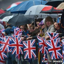 People holding umbrellas and Union Jacks
