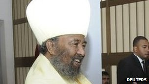 """Egypt""""s President Mohamed Mursi (R) shakes hand with Patriarch of the Ethiopian Orthodox Church Abune Paulos in Addis Ababa on 16 July 2012"""