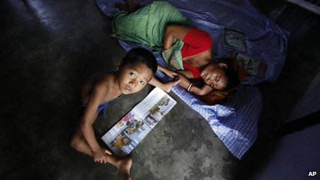 An Indian riot refugee woman sleeps as her child reads a book at a relief camp during India's ruling Congress party President Sonia Gandhi visit in Deborgaon in Kokrajhar, India, Monday, Aug. 13, 2012