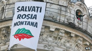 A Romanian demonstrator looks out a window next to a banner reading 'Save Rosia Montana'