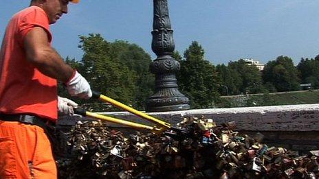 A workman cuts padlocks hanging hanging along the Ponte Milvio bridge in Rome, Italy, 10 September 2012