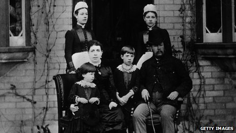 A Victorian family and their two maids pose on the doorstep of their house, 1875