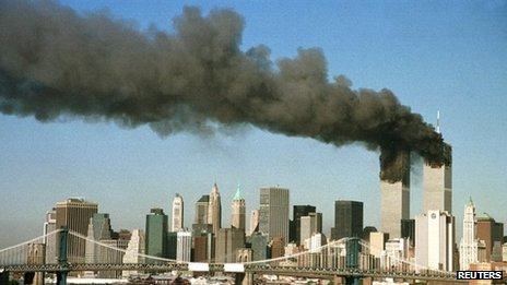 The towers of the World Trade Center pour out smoke shortly after being struck by hijacked airliners in New York in this 11 September 2001 file photograph