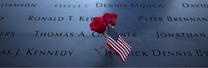 Roses and a U.S. flag are laid amid the names of the First Responders along the South Pool of the 9/11 Memorial in New York
