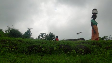 Woman with water vessel on head walking along top of hill