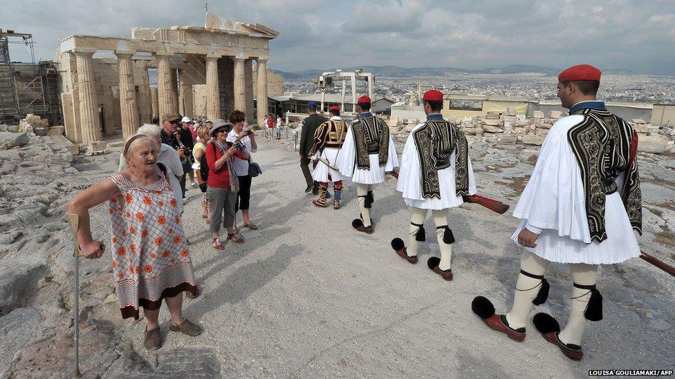 People watch Greek presidential guards leave the Acropolis