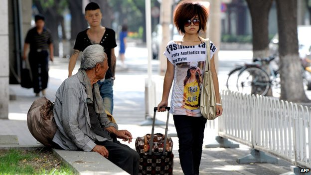 Rich woman walks down a Chinese street next to a poor man