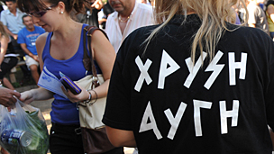 Golden Dawn members (R) hand out free food to Greek people after checking their IDs