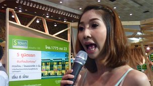 Ailsa Phaiboonnantanpong tries to attract a crowd to her stall at the Bangkok House and Condominium Show