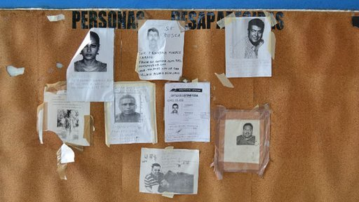 Photos of missing people on a wall outside Acapulco mortuary