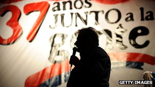 Jose Mujica - in silhouette - speaking at a rally to commemorate the formation of the Frente Amplio