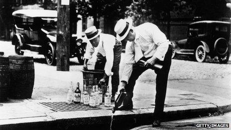 Men pour liquor down a drain in 1920