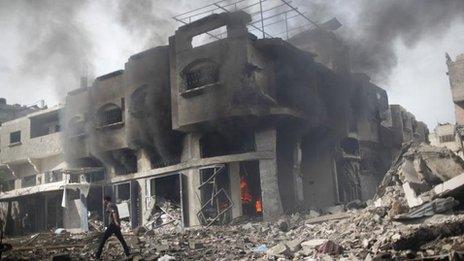 Palestinian man walks past house burning after Israeli air strike in Gaza City (18 Nov)