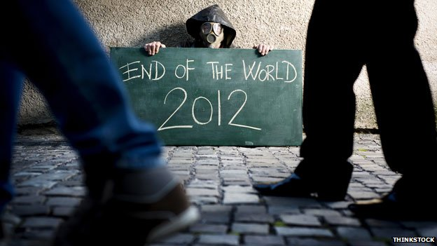 "Man in gasmask holding ""End of the world 2012"" sign"