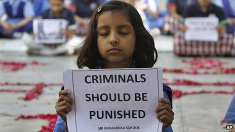 An Indian schoolgirl holds a placard during a prayer ceremony to mourn the death of a 23-year-old gang rape victim, at a school in Ahmadabad, India, Saturday, Dec. 29, 2012.