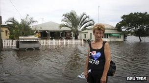 A residents stands in front of her flooded home in Bundaberg on 27 January 2013