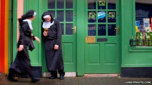 A man dressed as a nun drinks outside a pub