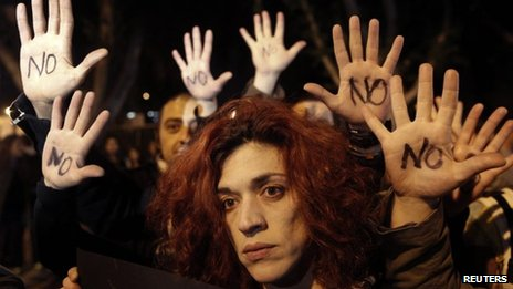 """Anti-bailout protesters raise their open palms showing the word """"No"""" after Cyprus""""s parliament rejected a proposed levy on bank deposits"""