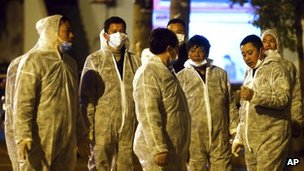 Workers in protective clothing chat during a culling operation as authorities detected the new bird flu strain in pigeons being sold for meat at a wholesale market in Shanghai on 5 April 5 2013