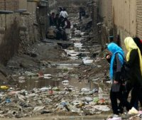 Women walk past heroin addicts