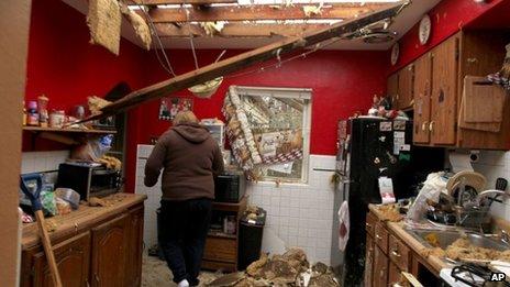A woman walks through her storm-damaged kitchen in Hazelwood, Missouri 11 April 2013