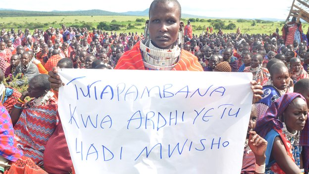 """A Maasai woman holds a sign that reads in Swahili: """"We will fight for our land until the end"""""""