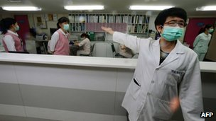 A nurse (R) introduces the front desk for the negative pressure isolation rooms section, which will be used to treat potential H7N9 avian influenza patients, at Taipei Hoping Hospital, 6 April 2013